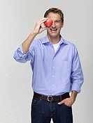 Young man holding apple, portrait