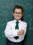 Boy 10-11 leaning against blackboard, smiling, portrait, close-up