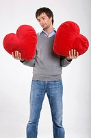 Young man holding heart-shaped cushions, portrait