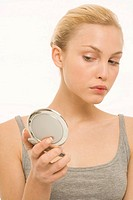 Woman looking at self in make-up mirror, portrait