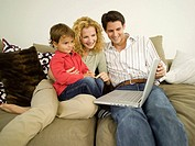 Young family in living room, father using laptop