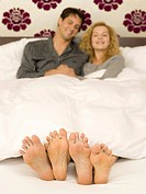 Young couple lying in bed, close-up of feet