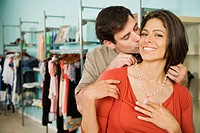 Hispanic man putting necklace on wife