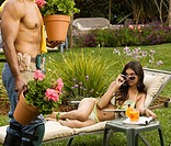 Hispanic woman looking at bare-chested gardener