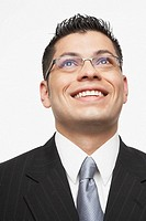 Hispanic businessman looking up