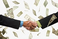 Businesspeople shaking hands in rain of money