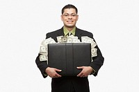 Hispanic businessman holding briefcase full of money
