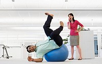 Businessman Falling Off Exercise Ball