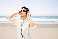 Asian man listening to headphones at beach