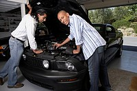 Multi-ethnic men looking under hood of car