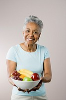 Senior African American woman holding fruit bowl