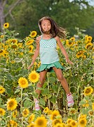 African girl jumping in flower patch