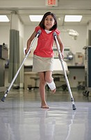 Hispanic girl walking with crutches