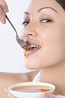 Mixed Race woman dripping honey on lips
