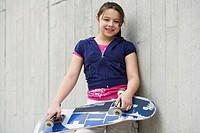 Mixed Race girl holding skateboard