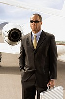 African American businessman in front of airplane