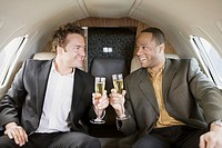 Multi-ethnic businessmen toasting on airplane