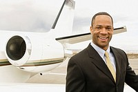 African businessman next to airplane