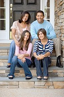 Hispanic family sitting on porch steps