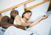 Multi-ethnic couple sleeping in bed
