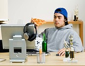 Mixed Race man eating pizza at computer desk
