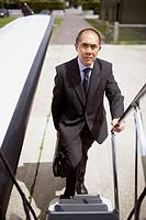 Asian businessman walking up airplane steps