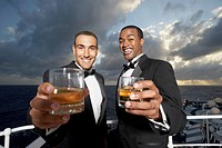 Multi-ethnic men in tuxedos toasting