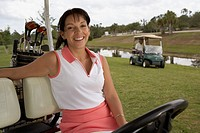 Hispanic woman sitting in golf cart