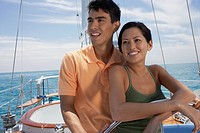 Multi-ethnic couple steering sailboat