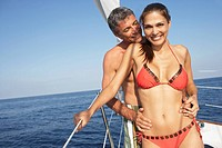 Multi-ethnic couple hugging on boat