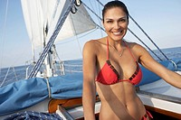 Hispanic woman in bikini on sailboat