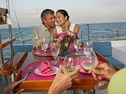 Multi-ethnic couple eating on sailboat