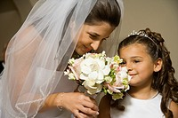Hispanic bride and young girl smelling flowers