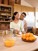 Multi-ethnic couple making orange juice