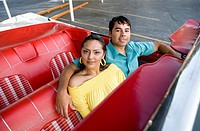 Hispanic couple sitting in convertible