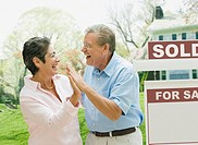 Senior couple high-fiving in front of new house