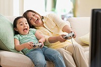 Hispanic mother and daughter playing videogames