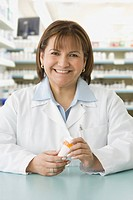 Hispanic female pharmacist holding medication
