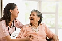 Senior Hispanic woman and nurse laughing (thumbnail)