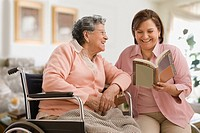 Hispanic woman reading to mother (thumbnail)
