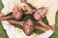 African American grandfather, father and son laying in grass