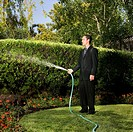 Hispanic businessman watering plants