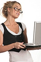 A woman wearing glasses holds a laptop computer