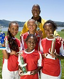 Multi-ethnic children holding soccer trophies