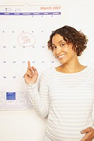 Pregnant Mixed Race woman next to calendar