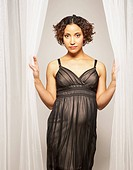 Pregnant Mixed Race woman standing in curtains