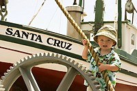 A little boy holding onto a rope in front of a wooden boat