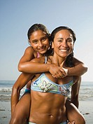 Hispanic mother giving daughter piggyback ride