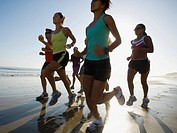 Multi-ethnic runners racing at beach (thumbnail)