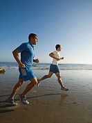 Hispanic men running at beach